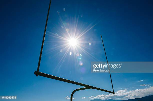 Silhouetted American football goal and blue sky