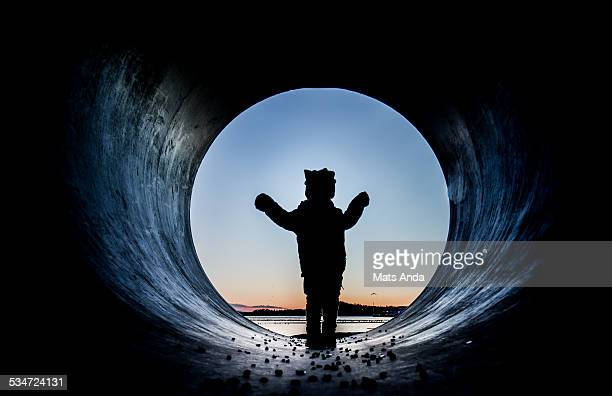 Silhouetted boy in pipe