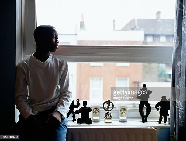 silhouetted boy near window - teen awards stock-fotos und bilder