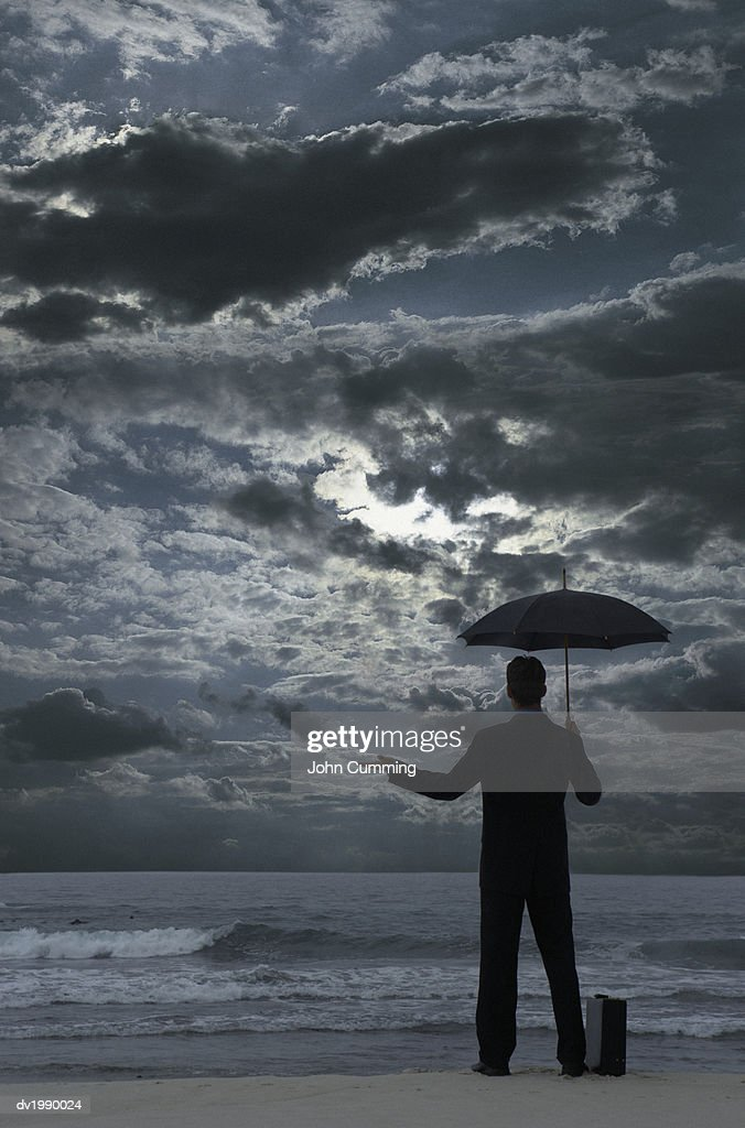 Silhouetted Businessman Standing on a Beach at Night, Holding an Umbrella and Checking for Rain : Stock Photo
