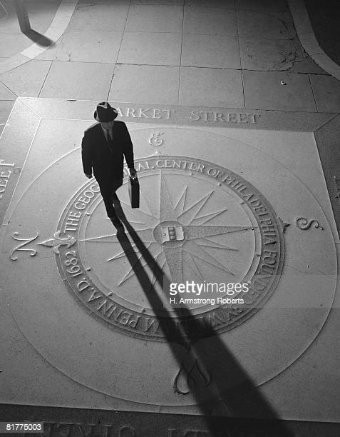 Silhouetted businessman with briefcase walking across compass in the sidewalk, elevated view, Philadelphia.