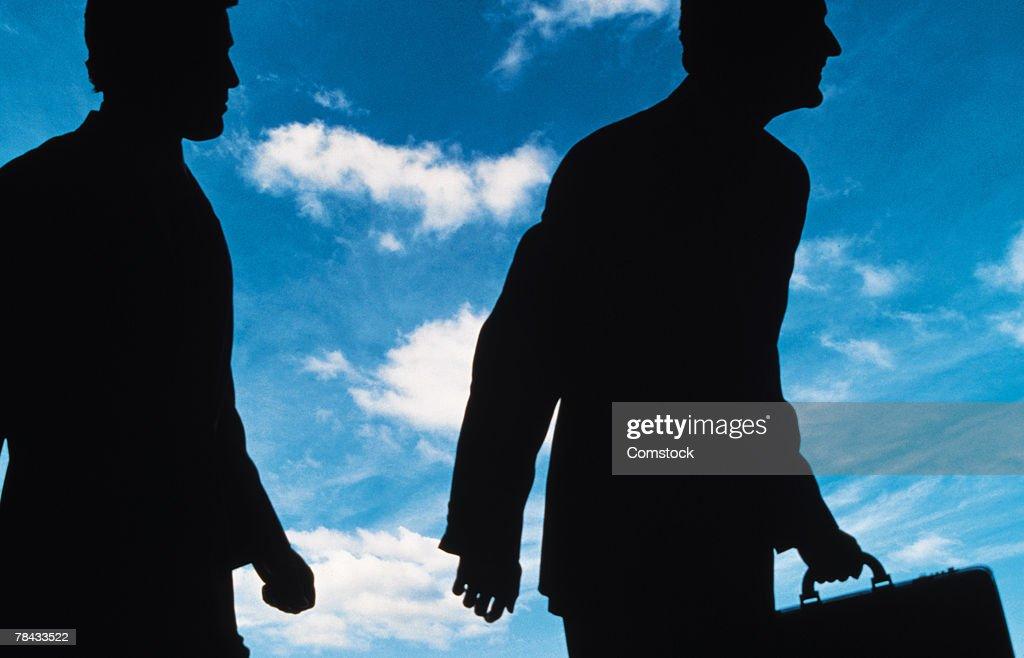 Silhouetted businessmen against sky : Stockfoto