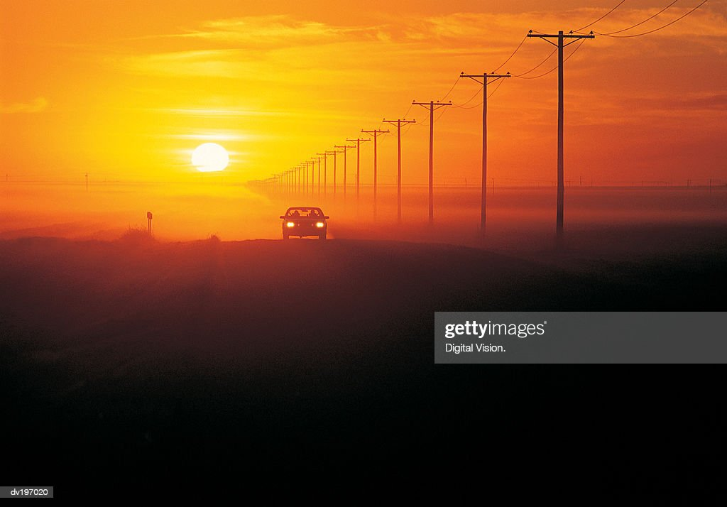 Silhouetted car with sunset : Stock Photo