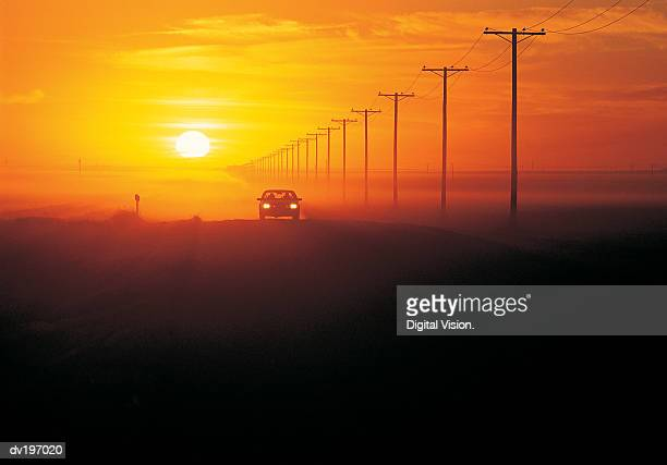 Silhouetted car with sunset