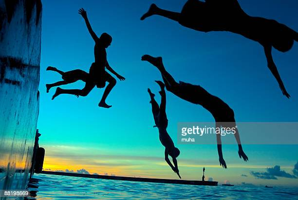 Silhouetted children diving into water