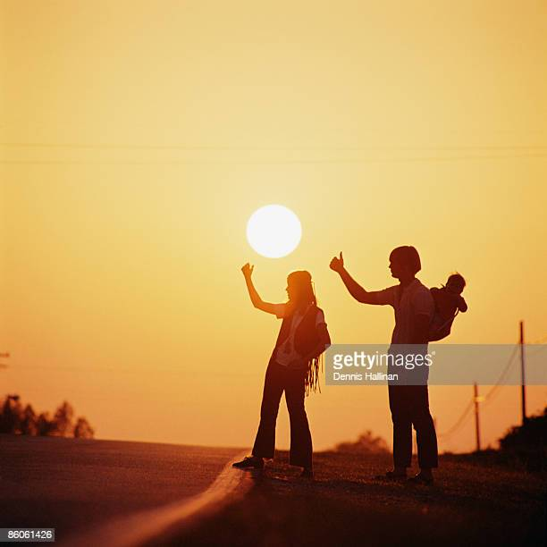 Silhouetted Couple Hitchhiking On Empty Road