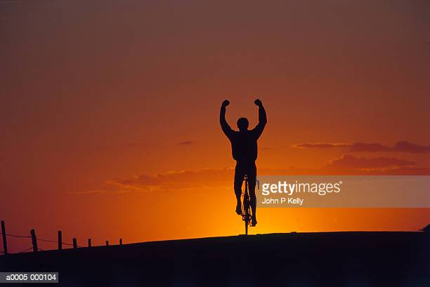 silhouetted cyclist - hands free cycling stock pictures, royalty-free photos & images