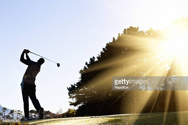 silhouetted early morning golfer makes his swing - golf swing stock pictures, royalty-free photos & images