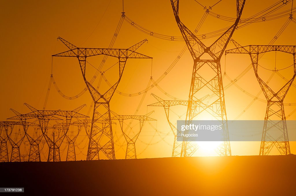 Silhouetted electricity pylon grid : Stock Photo
