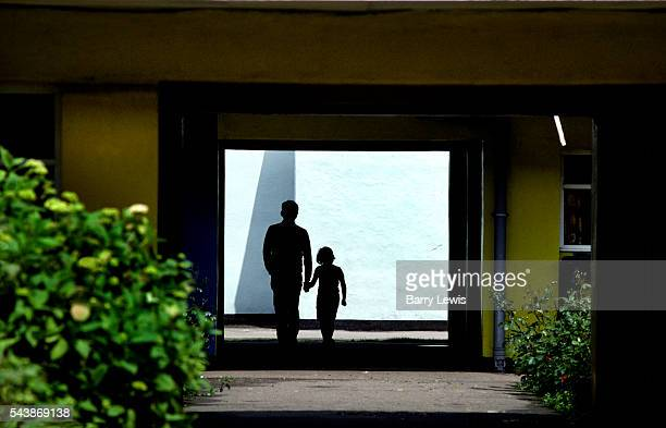 A silhouetted father and daughter holding hands walk through an archway between buildings with a white wall behind There are green bushes and a...