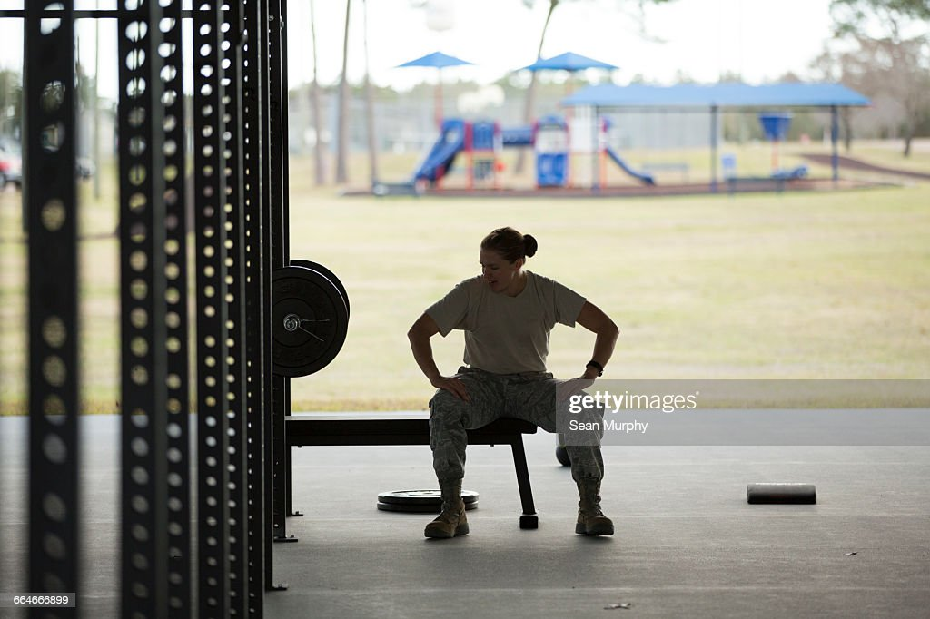 Silhouetted female soldier barbell training at air force military base : Stock Photo
