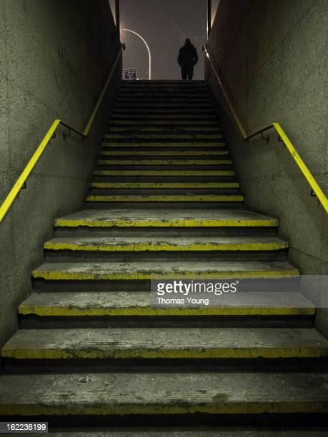 CONTENT] A silhouetted figure walks at the top of a long set of concrete yellowstriped stairs Taken on a cold winter night