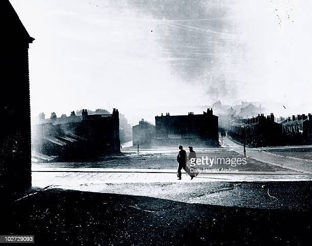 Silhouetted figures walk by a cleared blitz site, Liverpool, 21 November 1949. 'Join up of the cleared blitz site at Netherfield Road and Scotland...