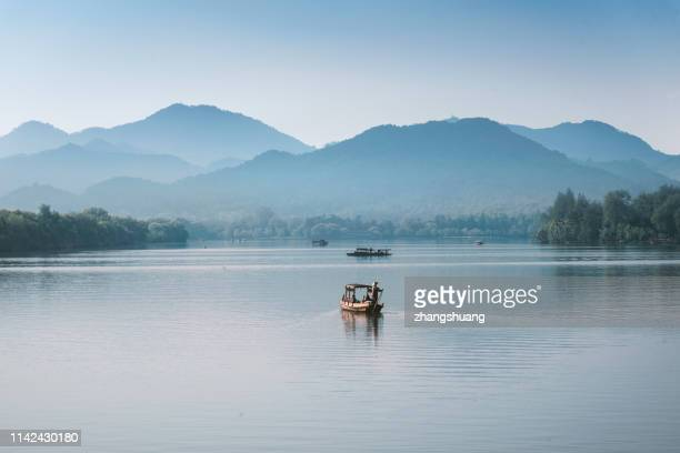 silhouetted fishing boat on west lake, hangzhou, china - shadow puppet stock photos and pictures