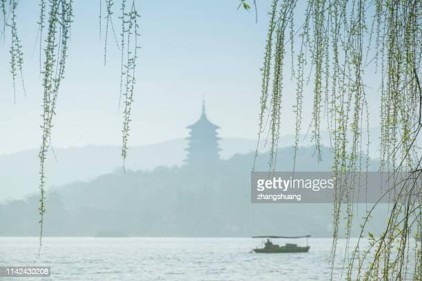 Silhouetted fishing boat on West lake, Hangzhou, China
