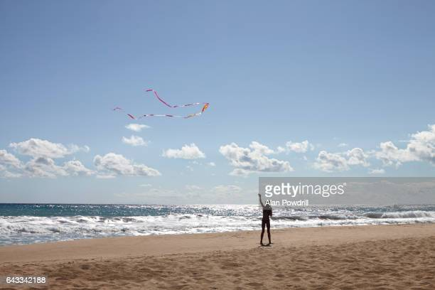 Silhouetted Girl Flying Kite on Beach