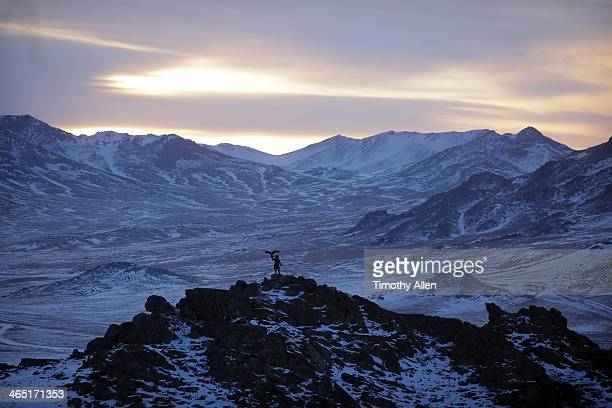 Silhouetted golden eagle hunter in epic mountains