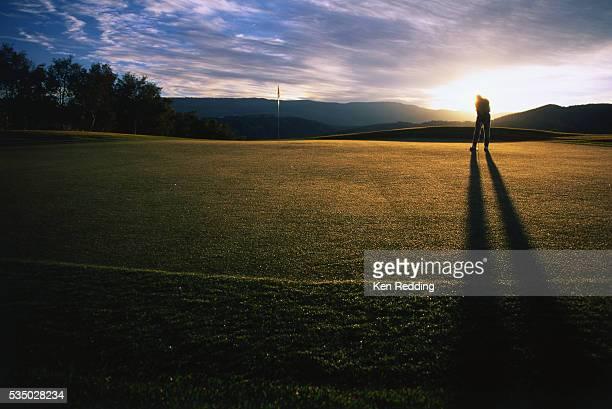 silhouetted golfer putting on the green - einlochen golf stock-fotos und bilder