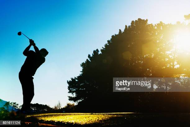 Silhouetted golfer teeing off at sunrise