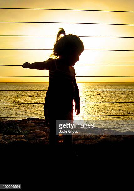 Silhouetted image of child at sunset