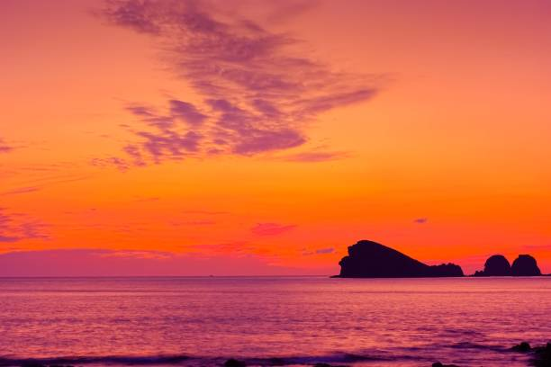 Silhouetted island in sea at sunset, Jeju Island, South Korea