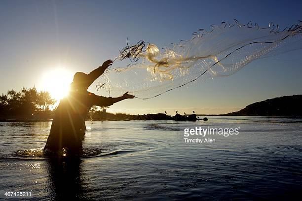 Silhouetted Laguna fisherman casts net at sunset