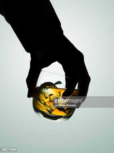 silhouetted male hand holding a glass of whiskey - alcohol abuse stock pictures, royalty-free photos & images