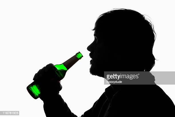 A silhouetted man about to drink from a beer bottle