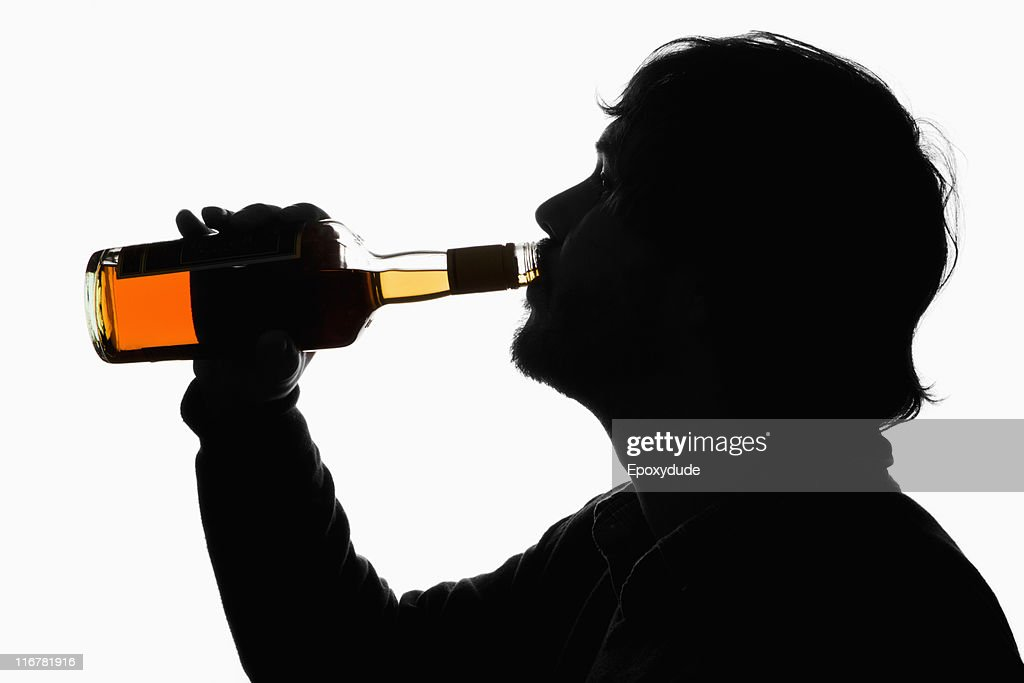 A silhouetted man drinking whiskey from the bottle : Stock Photo