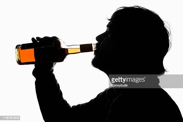 a silhouetted man drinking whiskey from the bottle - alcoolismo - fotografias e filmes do acervo