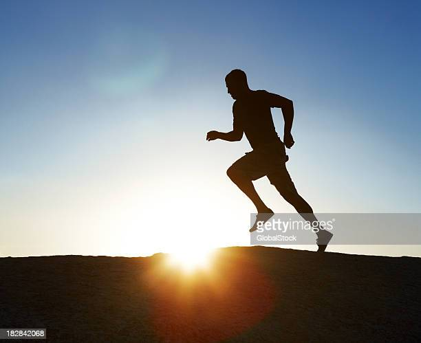 Silhouetted man running at sunset