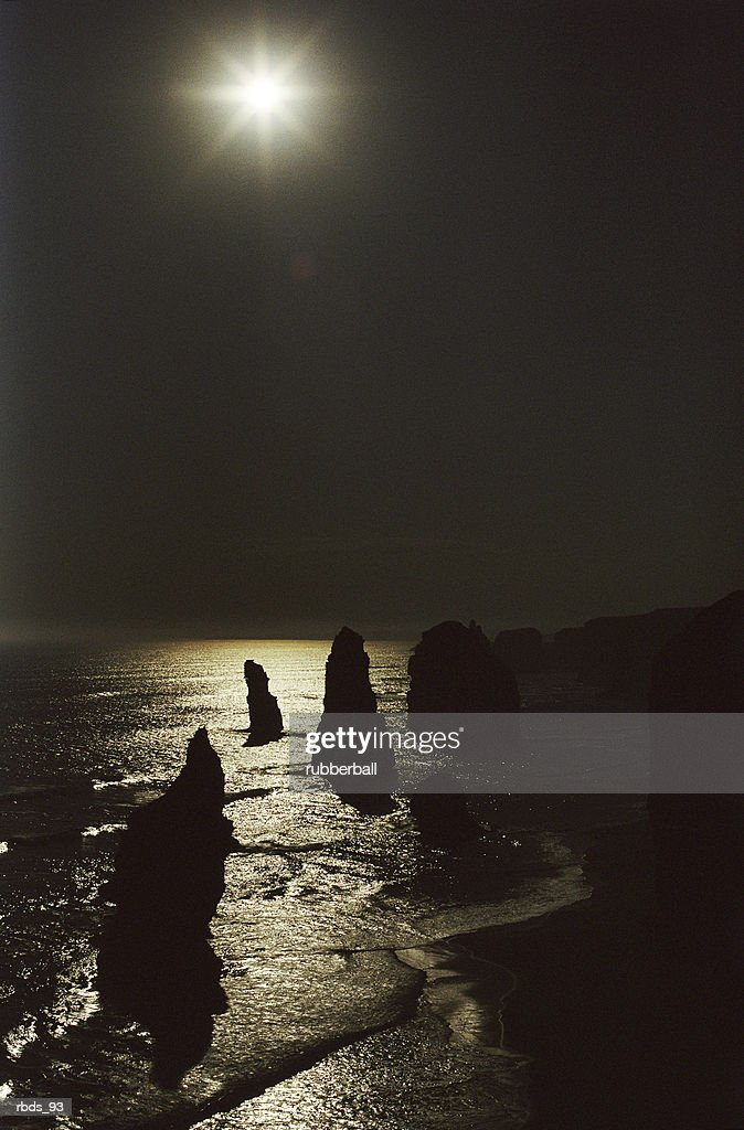 silhouetted monoliths rest in a sunlit seashore : Stockfoto