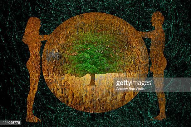 silhouetted naked people holding globe and tree - adamo e eva foto e immagini stock