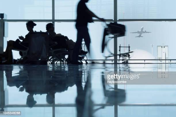 siluetas de pasajeros espera o retraso en el aeropuerto terminal de barcelona, españa - cambio horario fotografías e imágenes de stock