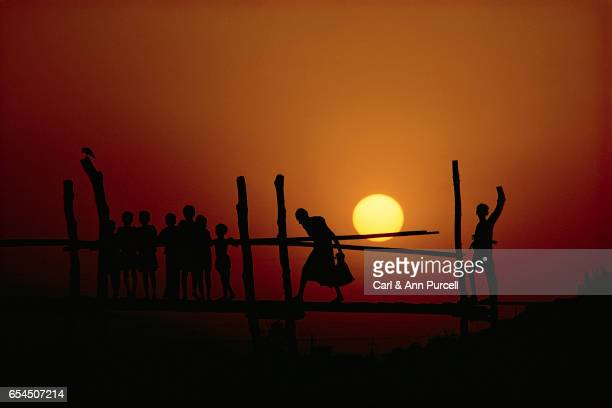 Silhouetted People on a Footbridge at Sunset