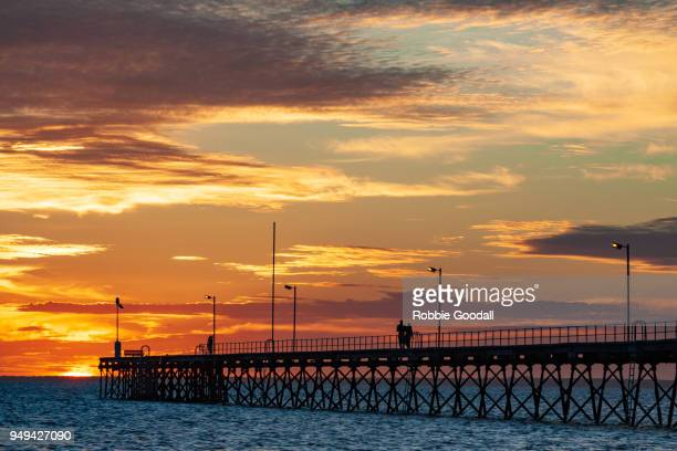 silhouetted people walking along jetty at sunset - ceduna, south australia - kangaroo island stock pictures, royalty-free photos & images