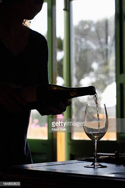 A silhouetted person pouring white wine into a glass at a wine tasting