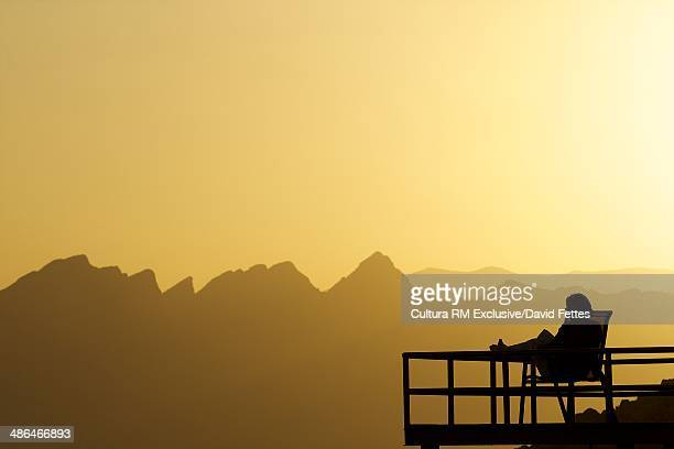 Silhouetted person sitting on balcony at sunset, Nizwa, Oman