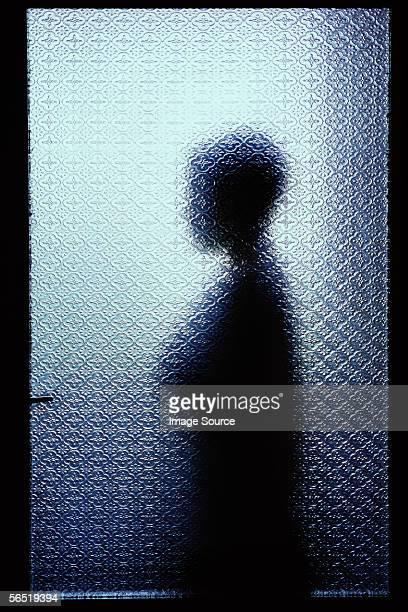 silhouetted person through window - onheilspellend stockfoto's en -beelden