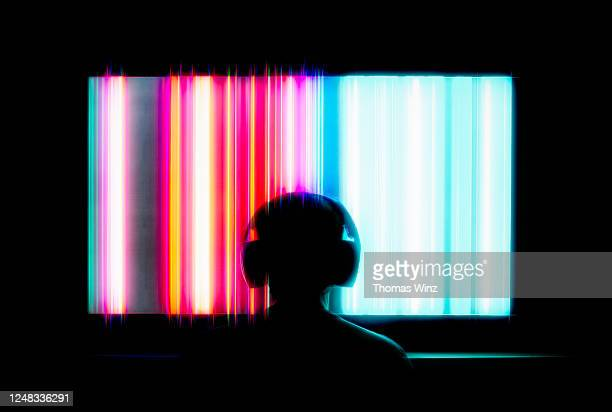 silhouetted person with headphones watching large tv screen - insight tv ストックフォトと画像