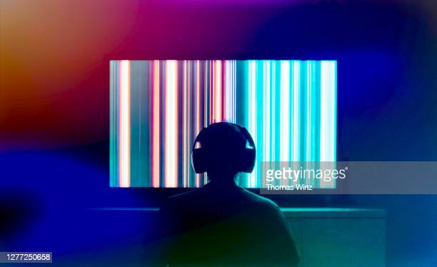 silhouetted person with headphones watching large tv screen - insight tv stock-fotos und bilder