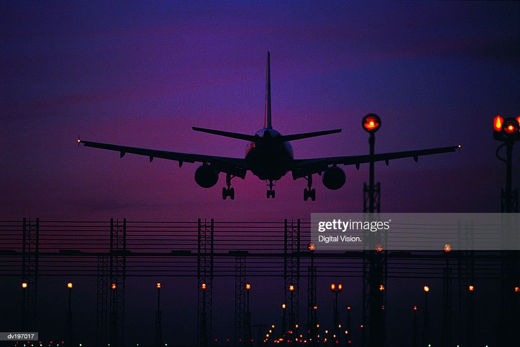 Silhouetted plane landing at night : Stock Photo