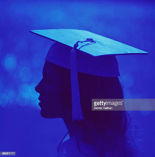 Silhouetted profile of woman wearing graduation cap