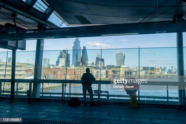 Silhouetted rail travellers look out of the wide glass windows of Blackfriars Station that stretches across the river Thames, and which overlooks a...