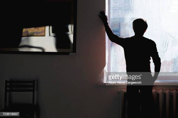 Silhouetted rear view of man looking through sunlit window