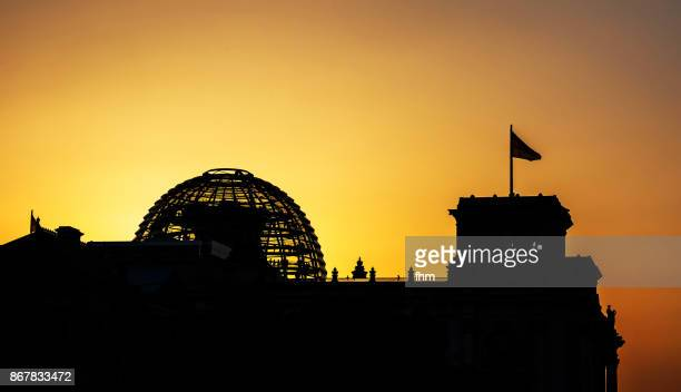 Silhouetted Reichstag building and dome in a verycolorful sunset (german parliament building) - Berlin, Germany