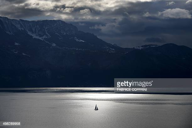 Silhouetted sailing boat is pictured on Lake Geneva with the French Alps as backgroud on November 22 2015 near Chexbres western Switzerland AFP...
