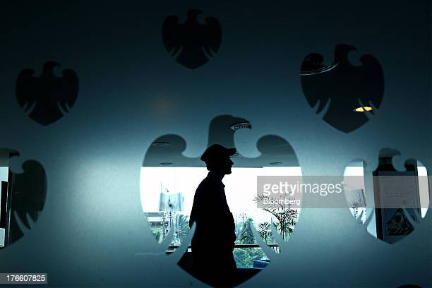 A silhouetted security guard is seen through the Barclays Plc logo on a frosted glass door inside a bank branch in Karachi Pakistan on Thursday Aug...