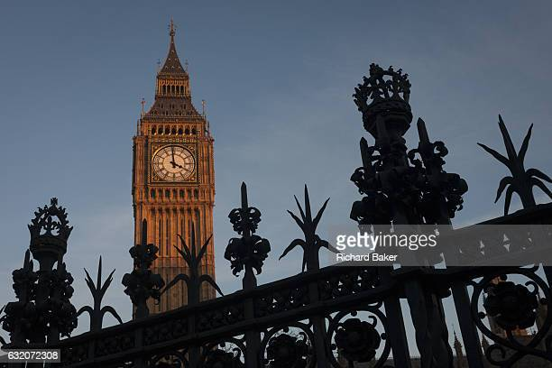 Silhouetted security railings featuring spikes and crowns and Elizabeth Tower of the British parliament on 17th January 2017 in London England The...