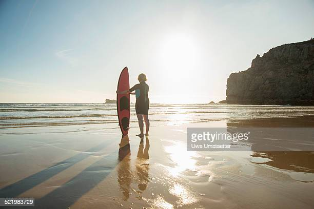 Silhouetted senior woman standing on beach with surfboard, Camaret-sur-mer, Brittany, France